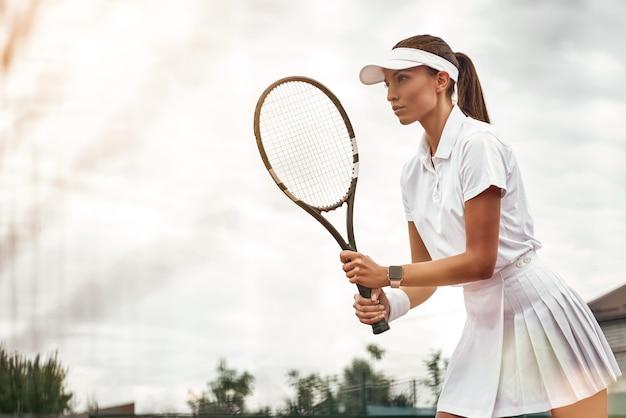 Женщина играет в теннис и ждет услуги