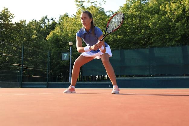 テニスをしてサービスを待っている女性。