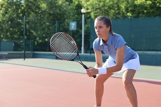 테니스를 치고 서비스를 기다리는 여자.