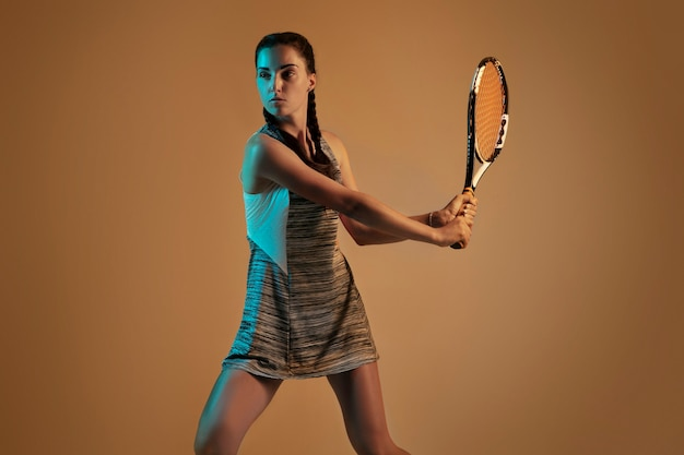 Woman playing tennis isolated on brown wall