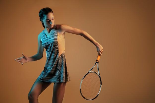 Donna che gioca a tennis isolato sulla parete marrone