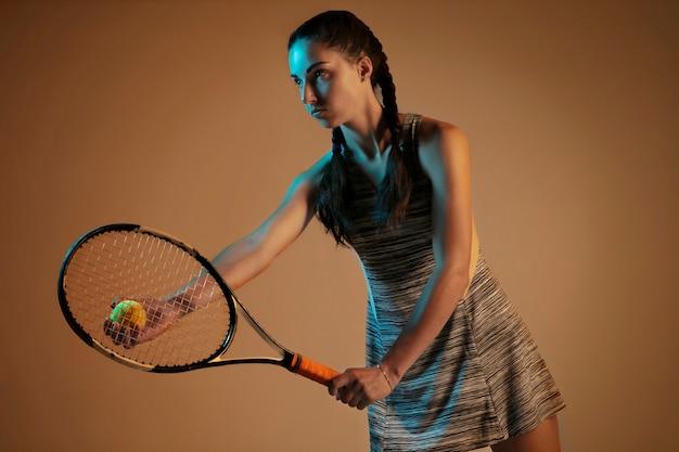 Женщина играет в теннис, изолированные на коричневой стене