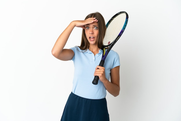 Woman playing tennis over isolated white wall doing surprise gesture while looking to the side