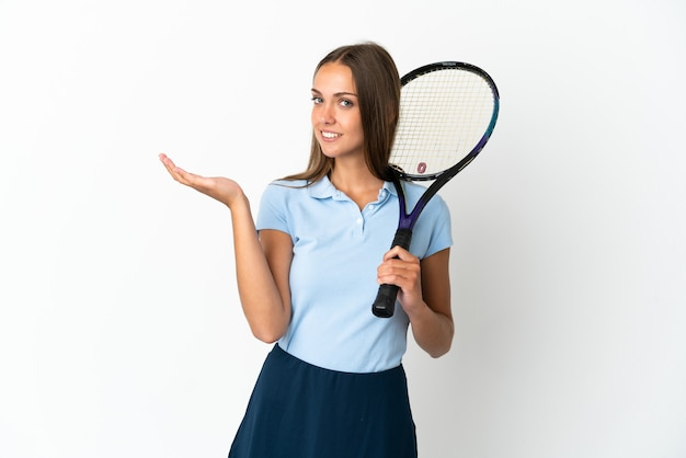 Woman playing tennis over isolated white wall extending hands to the side for inviting to come
