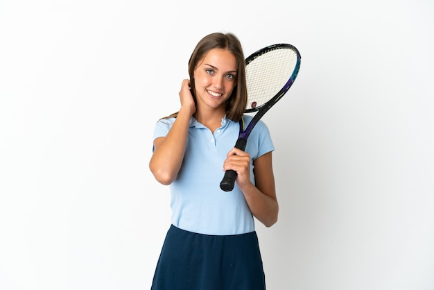 Woman playing tennis over isolated white wall laughing