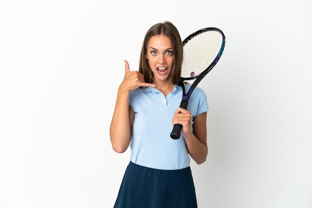 電話のジェスチャーを作る孤立した白い壁の上でテニスをしている女性。コールバックサイン