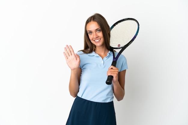 Женщина играет в теннис над изолированной белой стеной, салютуя рукой со счастливым выражением лица