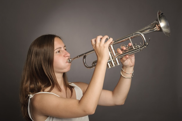 Woman playing trumpet on gray