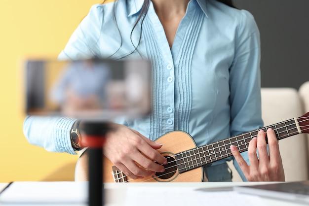 Женщина играет на гавайской гитаре и снимает на телефон. концепция музыкального блоггера