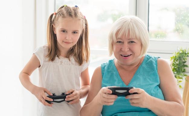 女性の孫娘とビデオゲームをプレイ