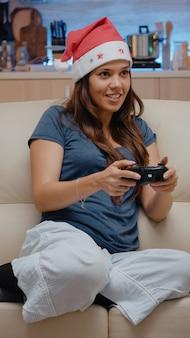 コントローラーとコンソールでビデオゲームをプレイする女性