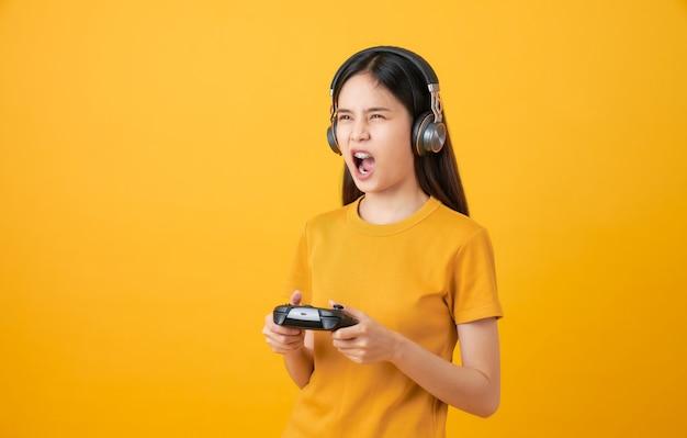 Женщина играет в видеоигры, используя джойстик с наушниками