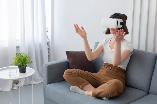 Woman playing a videogame while using vr goggles