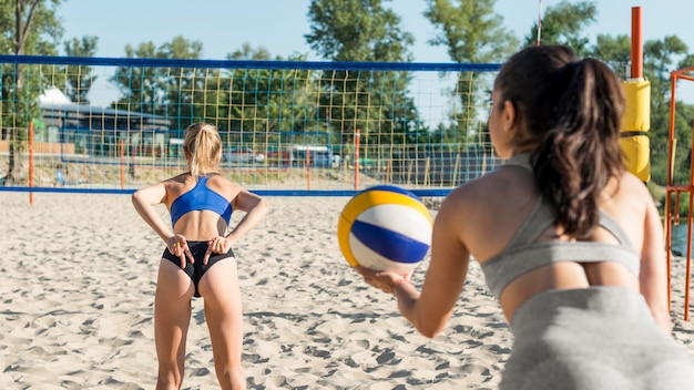 Woman playing volleyball and doing hand signals to teammate behind