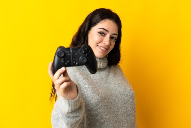 행복한 표정으로 노란색 배경에 컨트롤러가 격리 된 비디오 게임 컨트롤러를 가지고 노는 여자