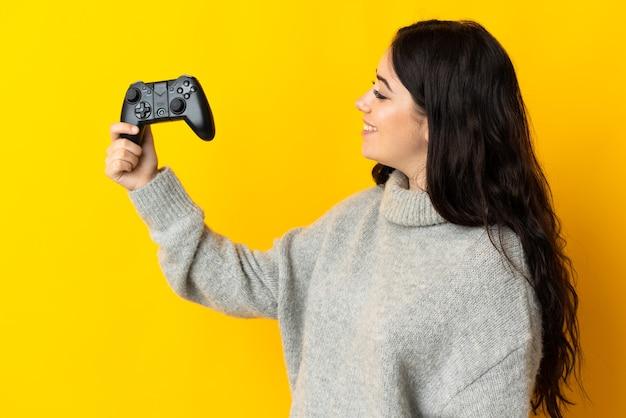 행복 한 표정으로 노란색 배경에 컨트롤러가 격리 된 비디오 게임 컨트롤러를 가지고 노는 여자