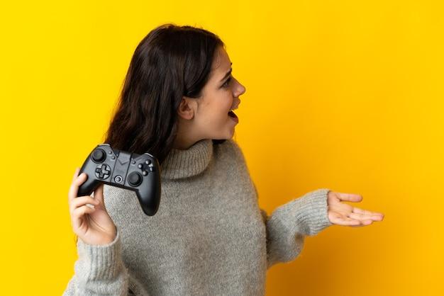 Женщина играет с контроллером видеоигры на желтом фоне с удивленным выражением лица
