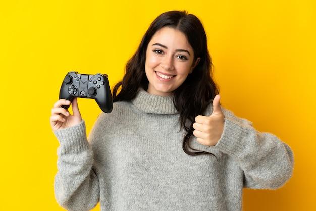좋은 일이 발생했기 때문에 엄지 손가락으로 노란색 배경에 비디오 게임 컨트롤러를 가지고 노는 여자