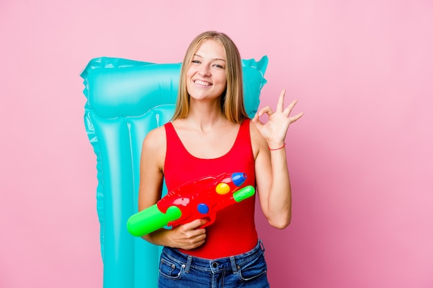 エアマットレスと水鉄砲で遊ぶ女性
