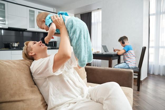 노트북에서 공부하는 십 대 동안 아기와 함께 노는 여자