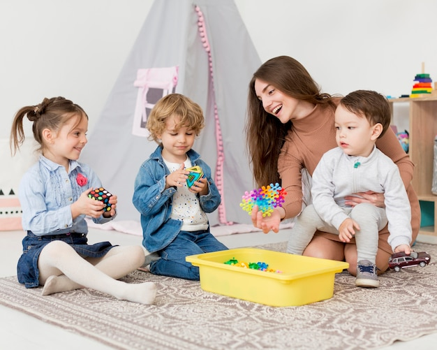 Woman playing with children at home with toys