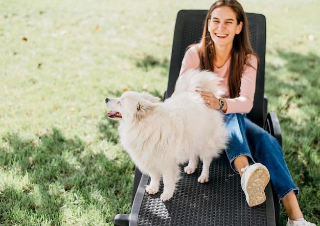 Женщина играет с милой собакой