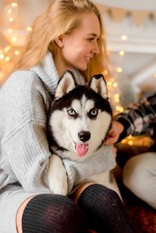 Женщина играет с собакой в спальне