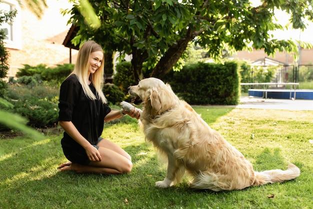 公園でラブラドール犬と遊ぶ女性