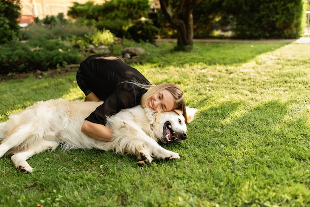 Женщина играет с собакой лабрадор на открытом воздухе