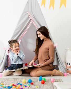 テントの中で幸せな若い女の子と遊ぶ女性