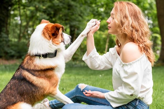 Женщина играет со своим лучшим другом в парке
