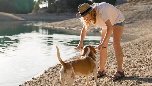 Женщина играет со своей собакой на берегу озера