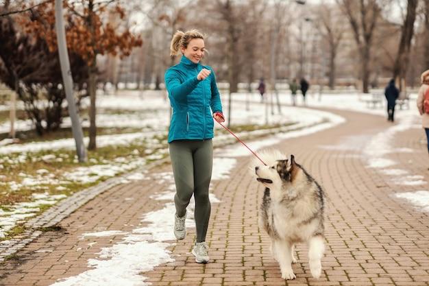 Женщина играет со своей собакой во время прогулки в парке в снежный зимний день. домашние животные, снег, дружба, мероприятия на выходных