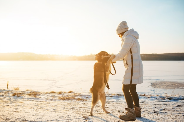 Woman playing with her dog on a winter day