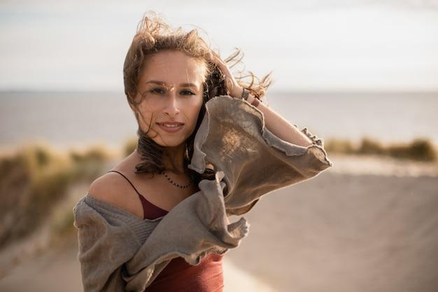 Donna che gioca con i suoi capelli durante il vento dietro uno sfocato