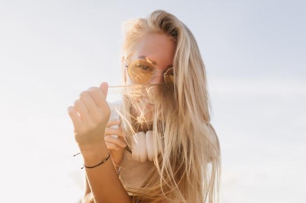 하늘 배경에 그녀의 머리를 가지고 노는 여자. 노란색 선글라스에 장난 백인 모델의 야외 촬영.