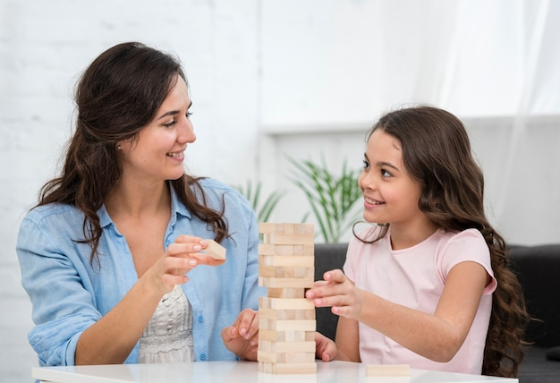 Woman playing with her little daughter a boarding game