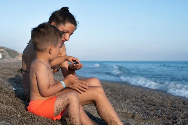 그녀의 유아 아들과 함께 노는 여자. 해변에서 아이와 함께 쉬고 있는 엄마의 모습.