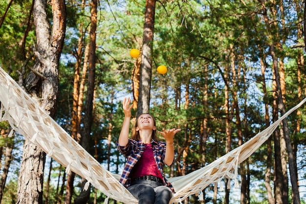 Woman playing with lemons in hammock