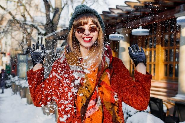 Woman playing with snow, having fun and enjoying holidays