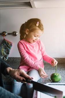 Donna che gioca con la verdura in cucina