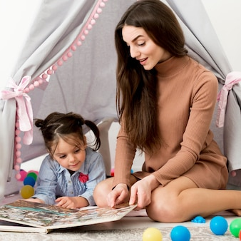 Woman playing with young girl in tent