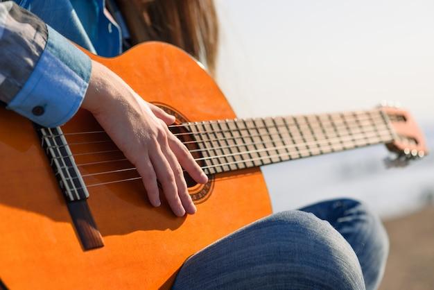 女性がギターを弾く海岸