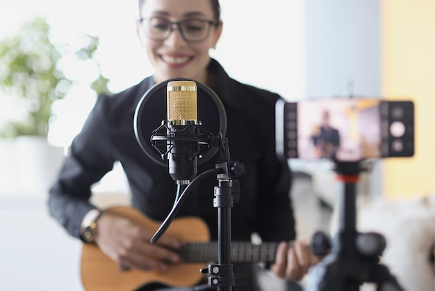 オンラインで学習しているスマートフォンのギターでビデオを録画しながら、女性がギターを弾き、歌う