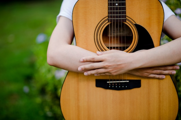 The woman plays the guitar happily.