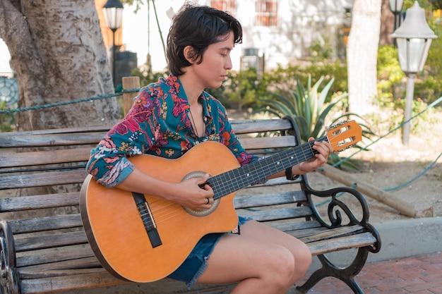 女性は公園でギターを弾く