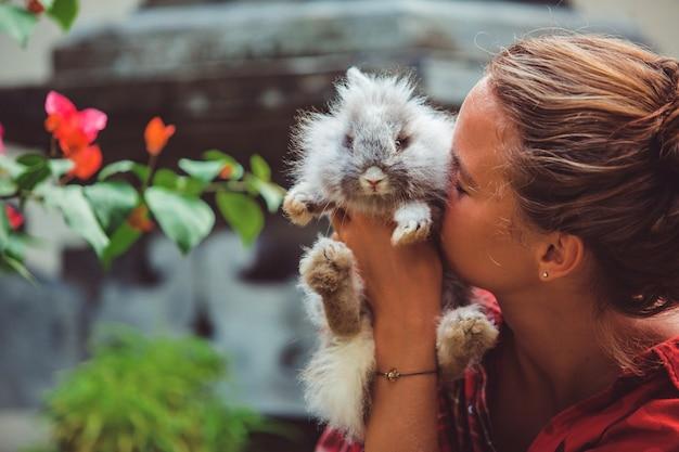 Женщина играет с маленьким кроликом.