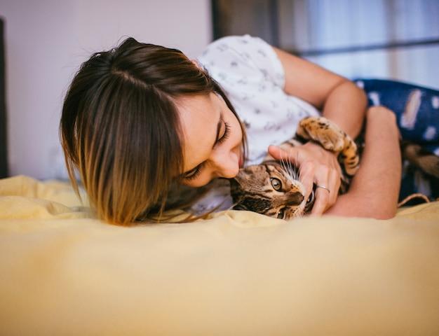 Женщина играет с бенгальской кошкой на кровати