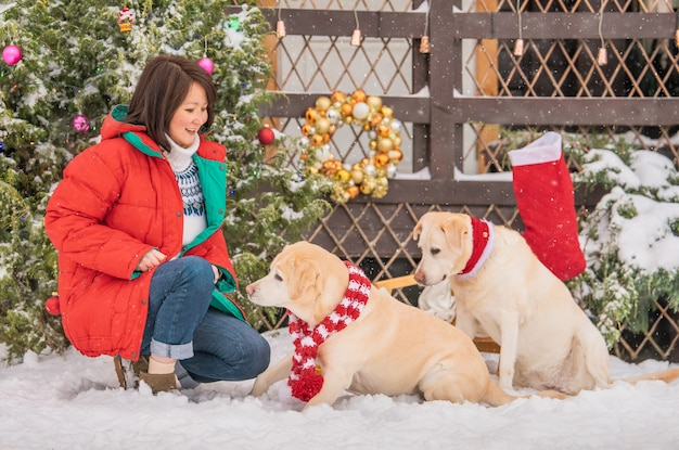 A woman plays with labradorsmi dogs near a decorated christmas tree during a snowfall in winter in the courtyard of an apartment building.