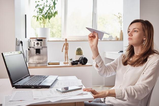 Женщина играет с бумажной простыней в домашнем офисе, откладывает удаленную работу Premium Фотографии